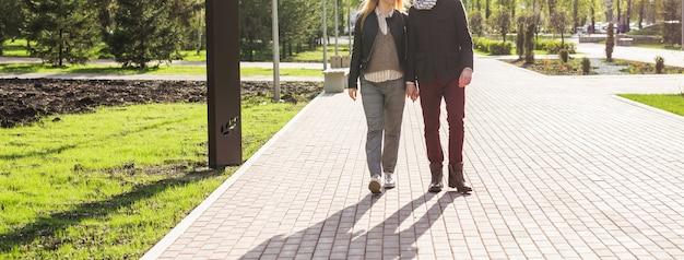 Elegante coppia innamorata che si tiene per mano per strada, la donna è incinta, banner