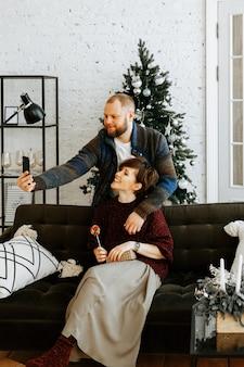 Un'elegante coppia innamorata scatta un selfie sul proprio smartphone sullo sfondo di un albero di natale a casa