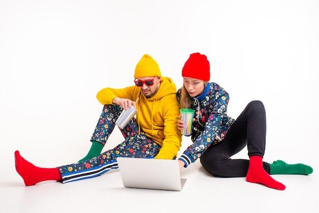 Elegante coppia di un uomo e di una donna in abiti colorati guardando lo schermo del computer portatile sul muro bianco
