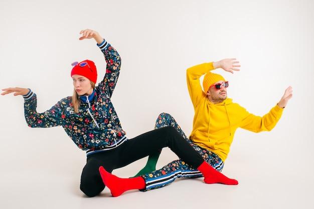 Elegante coppia di uomo e donna in abiti colorati in posa sul muro bianco