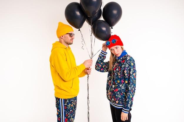 Elegante coppia di uomo e donna in abiti colorati in posa con baloons neri sopra il muro bianco