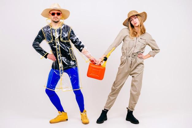 Elegante coppia di uomo e donna in cappelli di paglia in posa con annaffiatoio sul muro bianco
