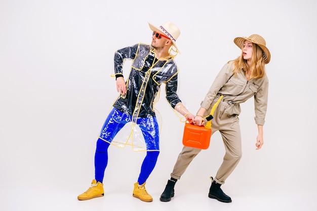 Elegante coppia di uomo e donna in cappelli di paglia in posa con annaffiatoio