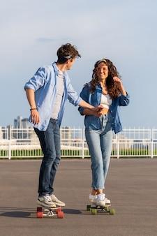 Elegante coppia di hipster alla moda in data skateboarding insieme sullo sfondo dell'orizzonte urbano. giovani adulti della città giovane uomo e donna sulla risata londboard si tengono per mano. concetto di relazione e stile di vita