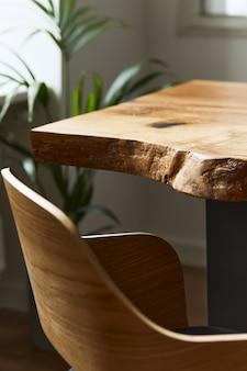 Composizione elegante e accogliente di tavolo in legno di quercia artigianale con sedie, pianta e pavimento moderno in splendidi interni di casa di design. modello.