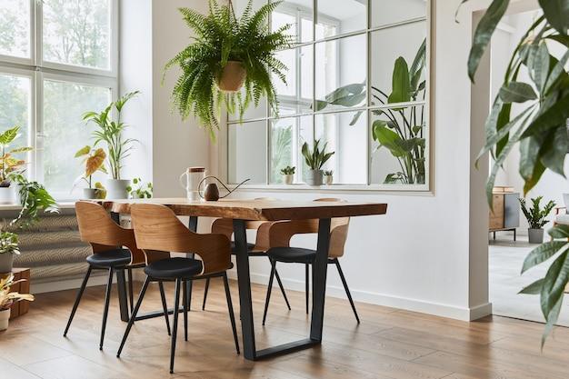 Interni eleganti e accoglienti della sala da pranzo con tavolo in legno di design artigianale, sedie, piante, divano in velluto, mappa poster e accessori eleganti in un arredamento moderno. modello.