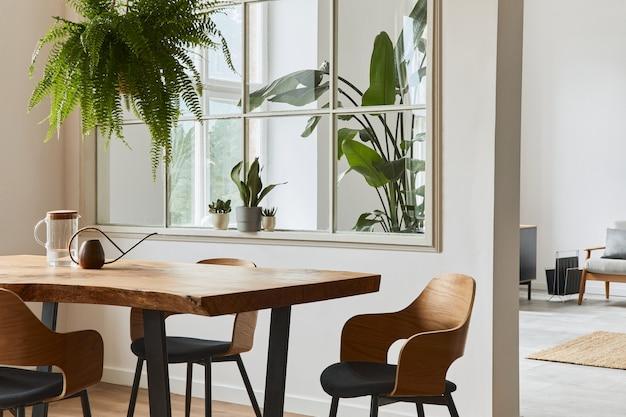 Interni eleganti e accoglienti della sala da pranzo con tavolo in legno di design artigianale, sedie, piante, divano in velluto, mappa poster e accessori eleganti nell'arredamento moderno della casa. modello.