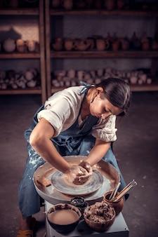 Un artigiano alla moda dimostra il processo di realizzazione di piatti in ceramica utilizzando la vecchia tecnologia. artigianato popolare.