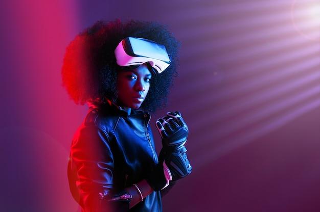 Elegante ragazza dai capelli scuri riccia vestita con giacca di pelle nera e guanti indossa gli occhiali per realtà virtuale sulla testa nello studio buio con luce al neon