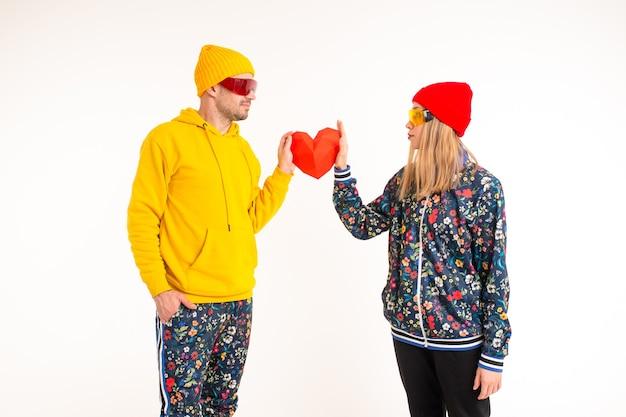 Elegante coppia carina di un uomo e di una donna in abiti colorati tenendo il cuore su sfondo bianco