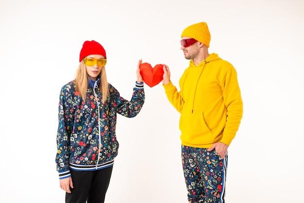 Elegante coppia carina di un uomo e di una donna in abiti colorati che tengono il cuore sopra il muro bianco