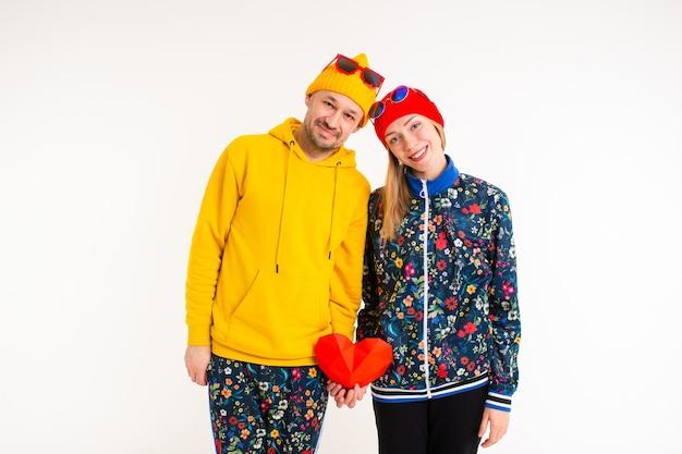 Elegante coppia carina di un uomo e di una donna in abiti colorati che tengono il cuore