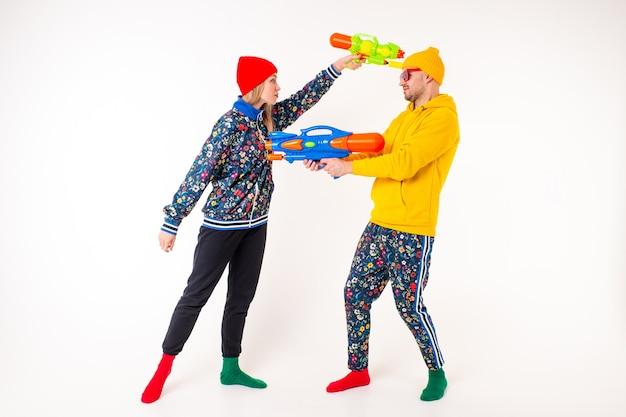 Elegante coppia carina di un uomo e di una donna in abiti colorati, giocando con pistole giocattolo