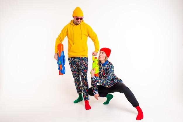 Elegante coppia carina di un uomo e di una donna in abiti colorati in posa con pistole giocattolo sul muro bianco