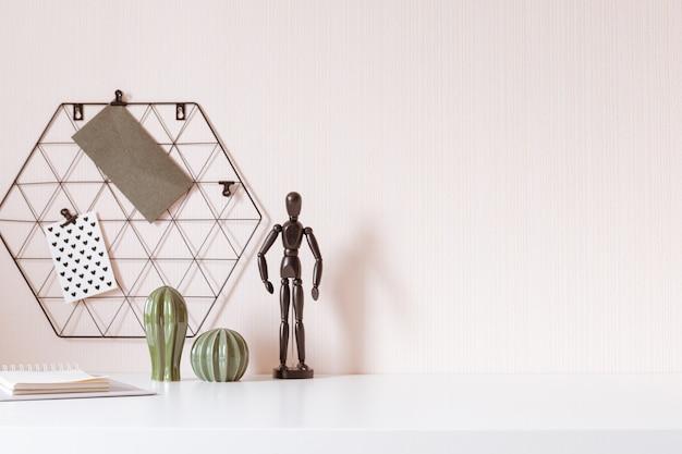 Interni alla moda scrivania con sfondo tavolo bianco con piante e foglie. interni moderni per l'home office