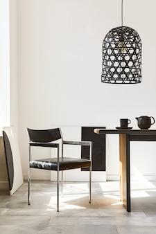 Interni eleganti della sala da pranzo con tavolo familiare in legno di design, sedie nere, teiera con tazza, finti quadri d'arte sul muro e accessori eleganti nell'arredamento moderno della casa. modello.