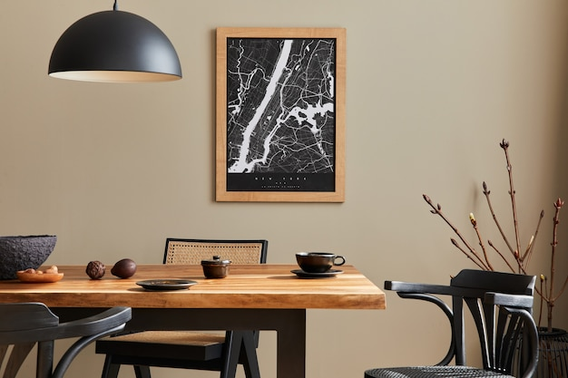 Interni eleganti della sala da pranzo con mappa, tavolo in legno di noce, sedie di design, tazza di caffè, decorazioni, stoviglie ed eleganti accessori personali nell'arredamento della casa..