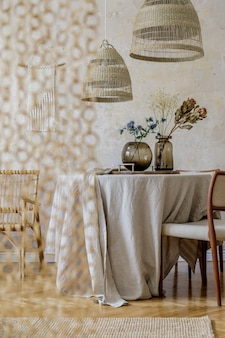 Interni eleganti della sala da pranzo con tavolo in legno, sedie di design, lampada a sospensione in rattan, fiori primaverili in vaso, bellissimi piatti, piante e decorazioni eleganti. wabi sabi concetto..