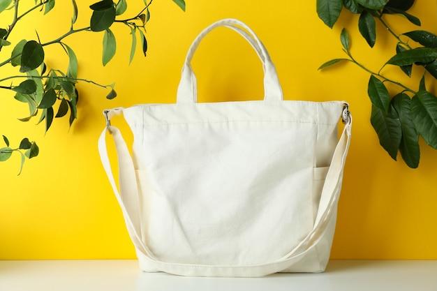 Elegante borsa eco sul tavolo bianco contro la superficie gialla