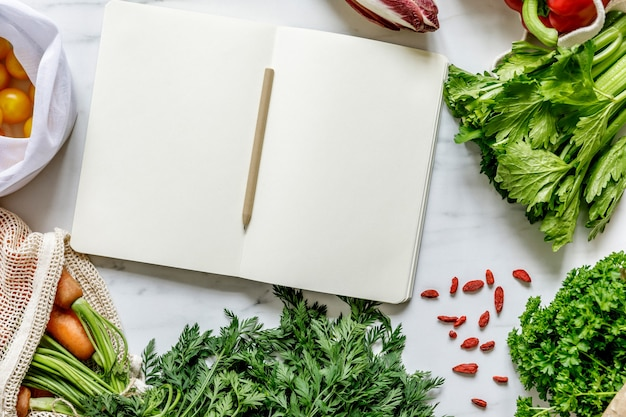 Elegante composizione ecologica sul tavolo in marmo con taccuino, sacchetti neutri zero rifiuti, semi, uova, erbe aromatiche, verdure bio e frutta fresca. prendersi cura della terra. stop alla plastica.