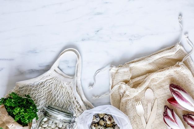 Elegante concetto di eco sul tavolo di marmo con sacchetti a zero rifiuti, noci, semi, uova, erbe aromatiche, verdure biologiche e frutta fresca. prendersi cura della terra. stop alla plastica. copia spazio.