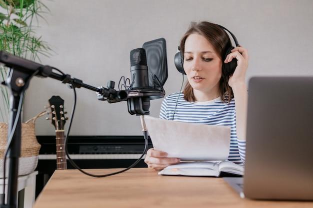 La donna caucasica elegante e istruita registra podcast in uno studio di registrazione o a casa sua il