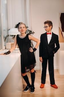 Un ragazzo e una ragazza eleganti ed eleganti stanno alla finestra all'interno della casa