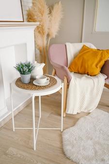 Elegante elegante eco composizione soggiorno con tavolo da colazione bianco tazza da caffè teiera falso camino fiori secchi piante erba pampa rosa cipria poltrona, coperta e cuscino