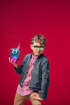 Elegante ragazzo emotivo con occhiali da sole e vestiti alla moda