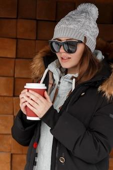 Donna alla moda europea giovane hipster in un cappello lavorato a maglia in una calda felpa in una giacca con pelliccia in occhiali da sole vicino a una parete di legno d'epoca che tiene una tazza rossa con bevanda calda. bella ragazza moderna.