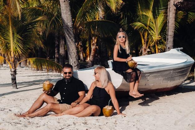 Una famiglia alla moda in abiti neri con noci di cocco in mano sulla spiaggia dell'isola di mauritius.bella famiglia sull'isola di mauritius nell'oceano indiano.