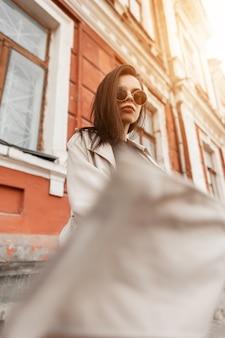 Elegante modella urbana giovane donna in occhiali da sole alla moda in trench beige sta girando in città la sera. ragazza attraente in abbigliamento casual che posa al tramonto vicino all'edificio d'epoca all'aperto.