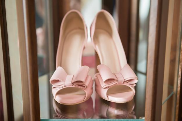 Tacchi alti alla moda rosa con un fiocco sullo sfondo della stanza, glamour, sposa, matrimonio
