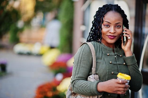 Le donne afroamericane alla moda alla moda in maglione verde e gonna nera hanno posto il caffè all'aperto con la tazza di caffè e parlano sul telefono cellulare.