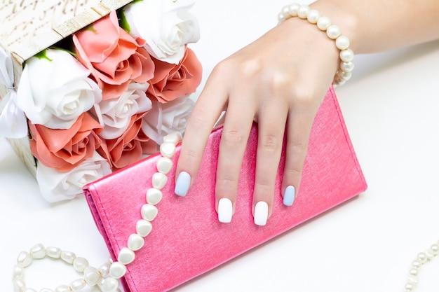 Elegante manicure femminile alla moda. belle mani di una giovane donna su uno sfondo o
