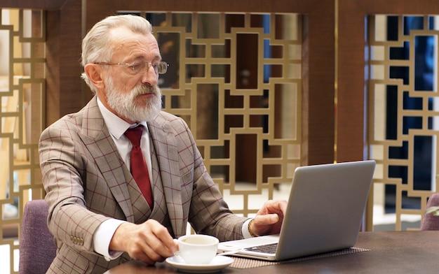 Elegante, alla moda focalizzato uomo anziano, pensionato, scrittore con gli occhiali e un abito classico che lavora su un computer portatile in un ufficio, ristorante, bar, primo piano