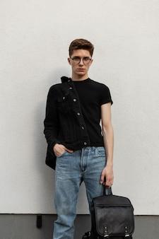 Elegante uomo alla moda in capispalla in denim con zaino vicino al muro