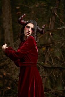 Ragazza modello elegante e alla moda nell'immagine di malefica in posa tra la foresta mistica - storia da favola, cosplay. halloween.