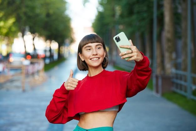 Elegante donna blogger avente videochiamata su strada, carina donna millenaria in maglione rosso che tiene sartphone e mostra il gesto giusto