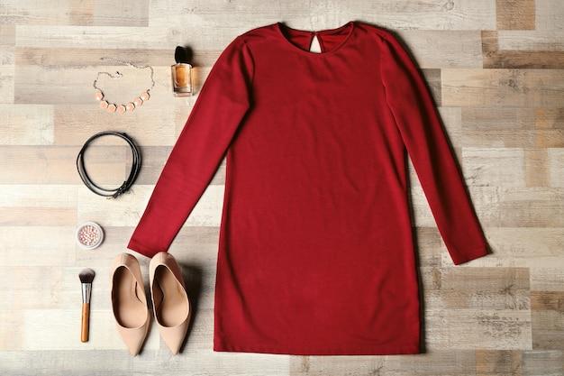 Vestiti femminili alla moda con accessori su fondo in legno