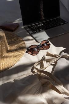 Eleganti occhiali da sole femminili, cappello di paglia, borsa per la spesa, laptop sul divano bianco con cuscini.