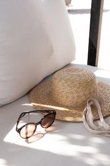 Eleganti occhiali da sole femminili, cappello di paglia, borsa shopper sul divano bianco con cuscini.
