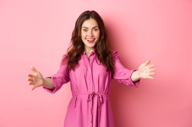 Elegante donna femminile che raggiunge le mani, allunga le braccia per accogliere un amico, vuole abbracciare o invitare qualcuno, in piedi contro il muro rosa.
