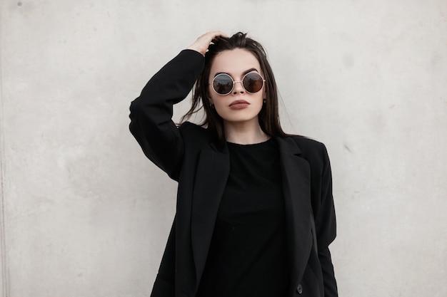 Elegante giovane donna fine con labbra sexy in occhiali da sole rotondi alla moda in blazer vintage nero in t-shirt alla moda si trova vicino al muro bianco in città. bella ragazza fresca in abito nero raddrizza i capelli.