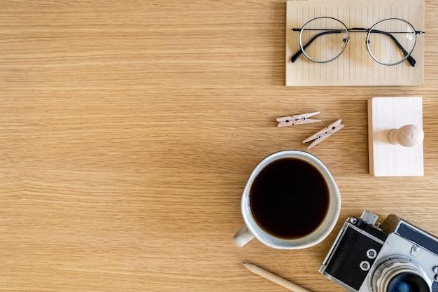 Elegante composizione aziendale piatta sulla scrivania in legno con macchina fotografica, cactus, penna, spazio copia e forniture per ufficio in un concetto moderno.