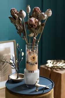 Composizione elegante e floreale di bellissimi fiori in vaso moderno sul pouf con accessori e mobili eleganti. concetto di fiore in soggiorno. pareti verdi. interior design. modello.
