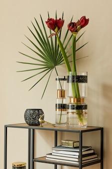 Composizione elegante e floreale di bellissimi fiori in vasi moderni sullo scaffale di design con accessori eleganti. concetto di fiore con ombre sul muro beige. interior design. modello.