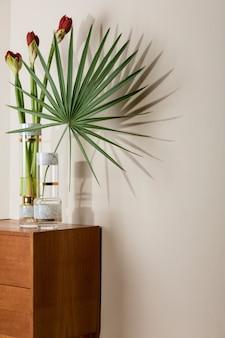 Composizione elegante e floreale di bellissimi fiori in vasi moderni sul comò in legno retrò con accessori eleganti. concetto di fiore con ombre sul muro beige. interior design. modello.