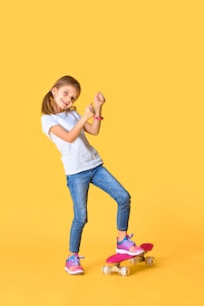 Elegante ragazza divertente che indossa t-shirt bianca, blue jeans e scarpe da ginnastica, in piedi su skateboard su uno spazio giallo
