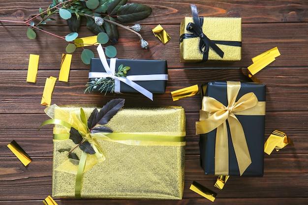 Eleganti scatole regalo e coriandoli sulla tavola di legno